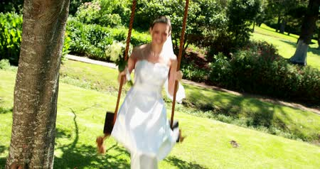 boldogság : Smiling bride sitting on a swing looking at camera on her wedding day Stock mozgókép