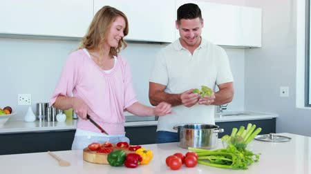 cooking pots : Smiling couple preparing a healthy dinner together at home in the kitchen
