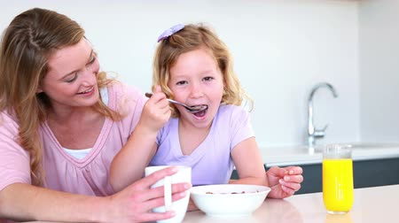kahvaltı : Pretty mother and daughter having breakfast at home in the kitchen