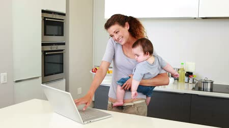 daireler : Mother holding her happy baby boy and talking on phone using laptop at home in the kitchen Stok Video