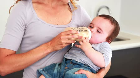 feed on : Mother feeding her baby boy his bottle at home in the kitchen Stock Footage