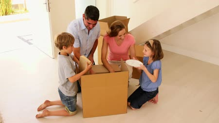guy home : Happy family opening box in their new home in their new home Stock Footage