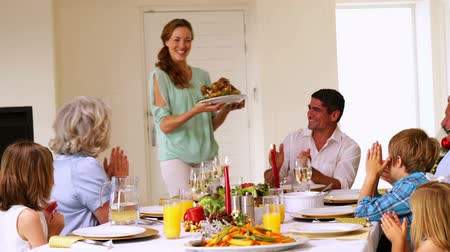 porce : Mother bringing turkey to dinner table at christmas at home in the dining room