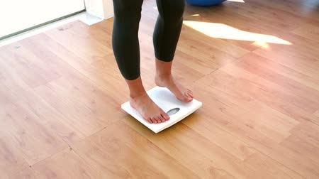 fogyás : Woman stepping on scales in slow motion