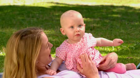 holding : Mother lying with her baby girl in the park in slow motion