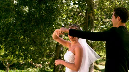 подвенечное платье : Happy newlywed couple dancing in the park in slow motion