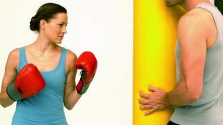 eğitici : Fit woman punching a bag held by trainer in slow motion