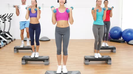 aeróbica : Aerobics class stepping together led by instructor and lifting dumbbells at the gym