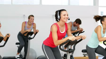 fejhallgató : Spinning class in fitness studio led by energetic instructor at the gym