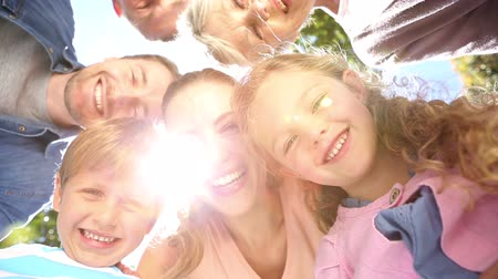 definíció : Extended family standing in the park together smiling down at camera on a sunny day Stock mozgókép