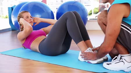 feminino : Fit woman doing sit ups with trainer at the gym