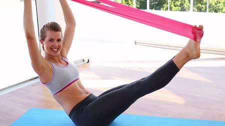esneme : Fit woman doing pilates with resistance band at the gym