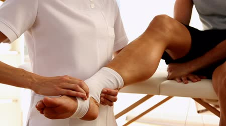terapeuta : Man getting his ankle wrapped by the physiotherapist in therapy room