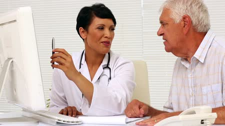physicians : Doctor explaining something on computer to patient in office at the hospital