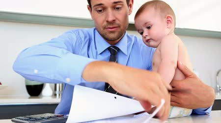 banknoty : Stressed father calculating bills with his baby at home in the kitchen