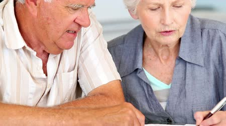 adósság : Senior couple using laptop to pay their bills at home in the kitchen