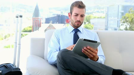 tabletler : Businessman waiting to go on a business trip using his tablet in the office Stok Video