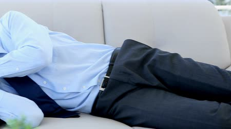 podnikatel : Businessman sleeping on the couch in the office