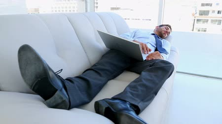 napping : Businessman sleeping on couch with his laptop in the office