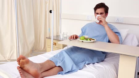 çatal : Patient sitting in bed having his lunch in the hospital ward Stok Video