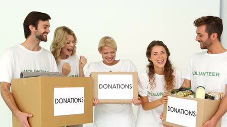 dobrovolník : Team of volunteers holding donation boxes and cheering on white background