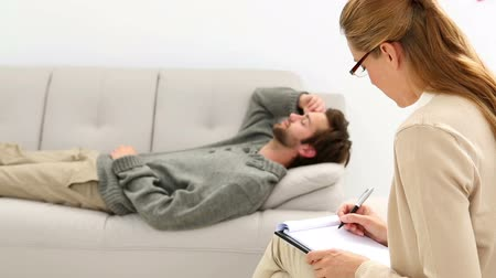 gyógyász : Young man lying on sofa talking to his therapist at therapy session