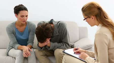 терапия : Young unhappy couple talking with their therapist at therapy session
