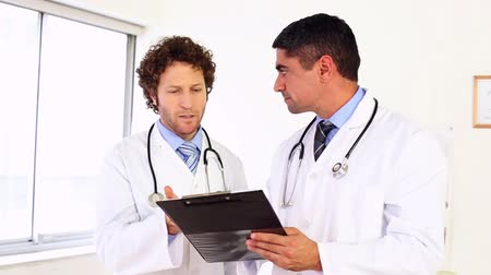 сотрудники : Doctors discussing something on clipboard in the office at the hospital