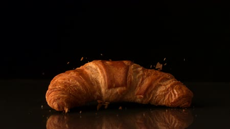 kruvasan : Croissant falling onto black surface in slow motion