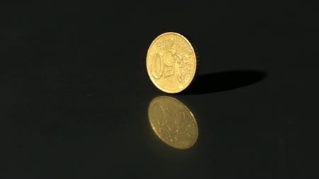 монета : Euro coin spinning on black surface in slow motion