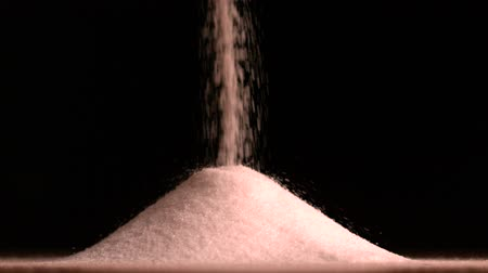 sůl : Sugar pouring on black background in slow motion