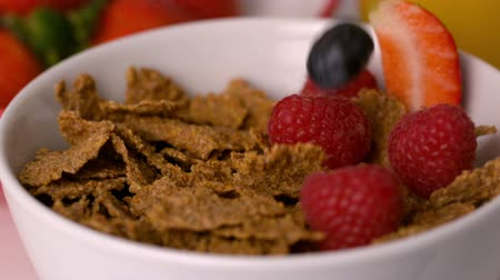 cereais : Berries pouring into cereal bowl at breakfast table in slow motion Vídeos