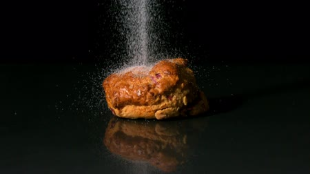 bolinho : Sugar sprinkling on scone on black background in slow motion
