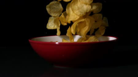 miska : Chips falling into bowl on black surface in slow motion
