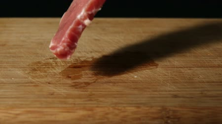 holding onto : Pork chop falling onto wooden table in slow motion Stock Footage