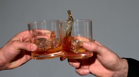 viski : Men clinking whiskey glasses on grey background in slow motion Stok Video