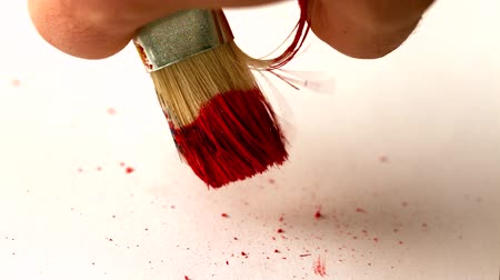 cákanec : Finger flicking red paint off brush in slow motion