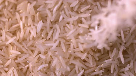 damlatma : White rice pouring onto more in slow motion