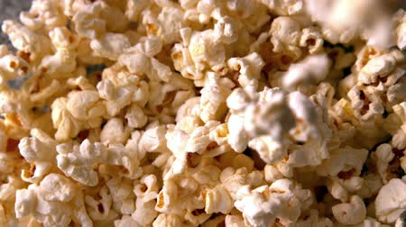 попкорн : Salty popcorn pouring onto more in slow motion
