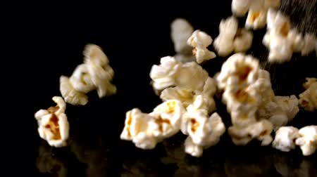 sůl : Popcorn and salt pouring onto black surface in slow motion