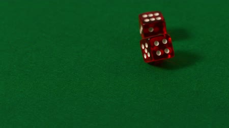 szerencsejáték : Red dice rolling on casino table in slow motion