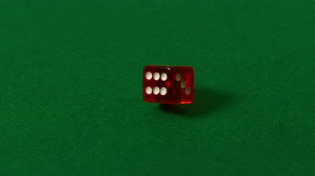 tablo : Red dice spinning on casino table in slow motion