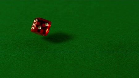 yuvarlanma : Red dice rolling on casino table in slow motion