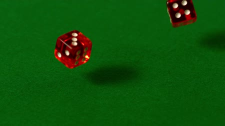 yuvarlanma : Red dice falling on casino table in slow motion