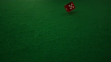 dobókocka : Red dice rolling towards camera on casino table in slow motion