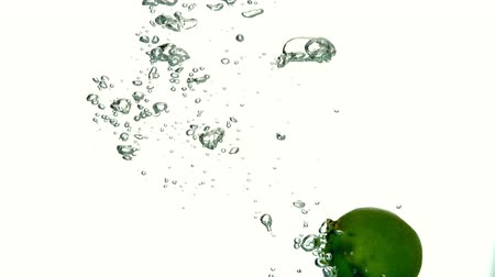 calcário : Lime plunging into water on white background in slow motion