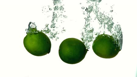 fresh water : Limes plunging into water on white background in slow motion