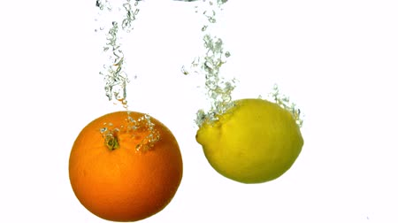 pomarańcza : Orange and lemon plunging into water on white background in slow motion
