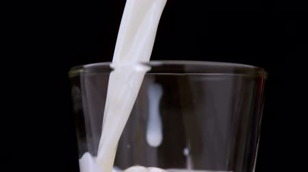 cálcio : Milk pouring into a glass in slow motion