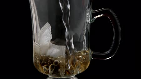 black tea : Hot water pouring over tea bag in glass in slow motion
